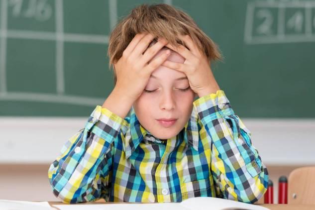 boy covering his eyes in school