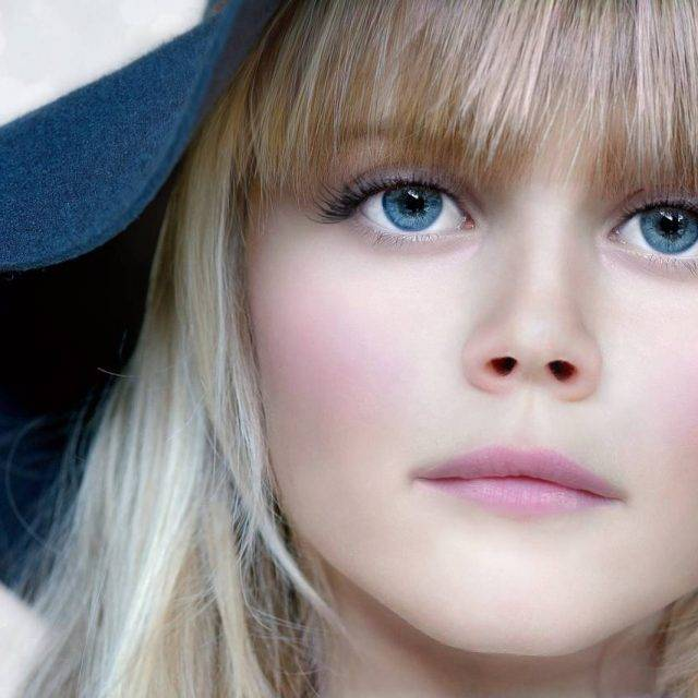 close up on beautiful blonde girl with blue eyes and matching blue hat
