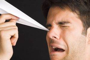 man poking eye with paper airplane
