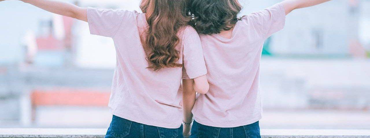 two young girls arms spread