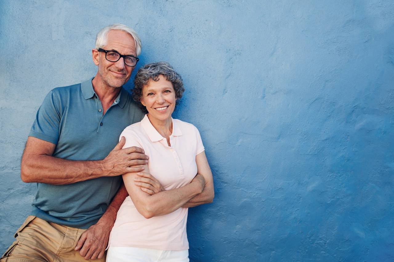 older couple waiting for diabetic eye exam in front of blue background
