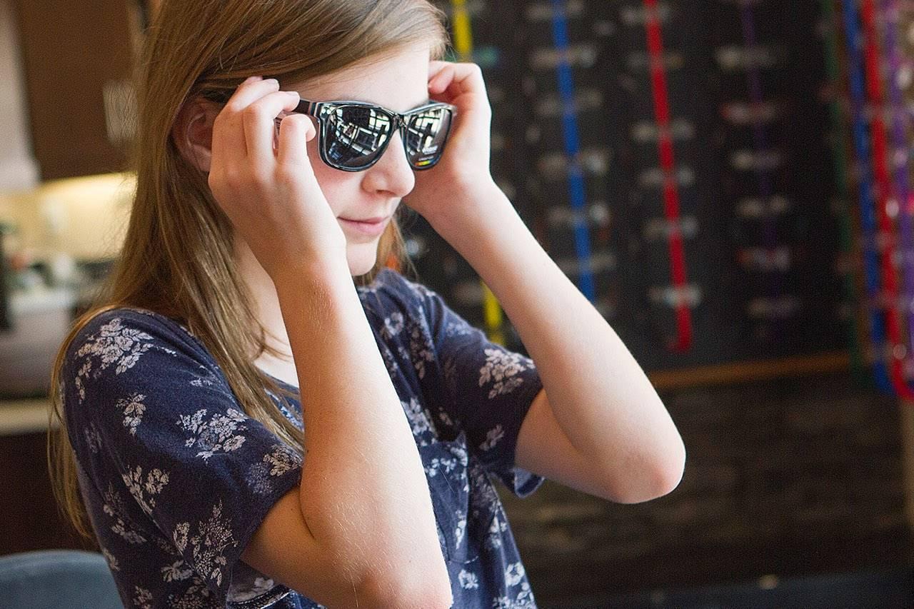 teenage girl trying on sunglasses