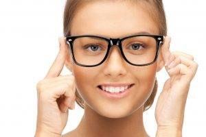 woman trying on glasses at her eye exam