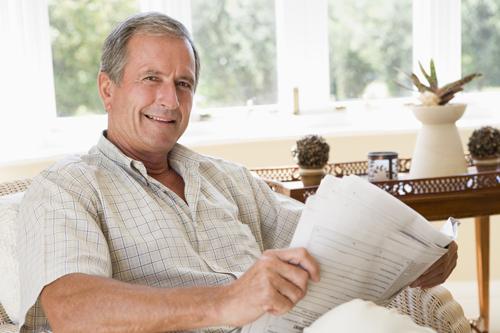 Man in living room reading newspaper smiling ft lauderdale fl