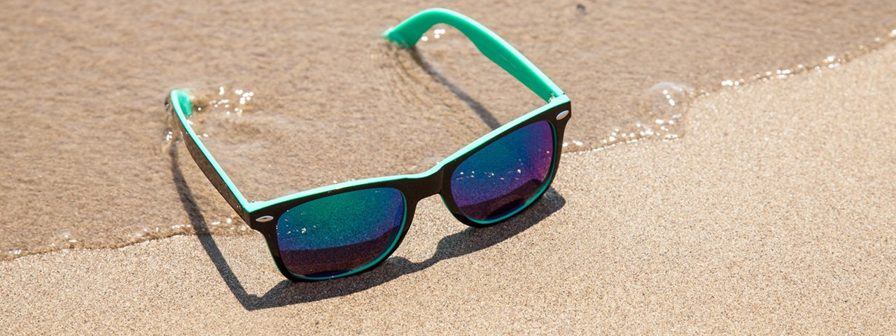 blue_sunglasses_sandy_beach_1280x480