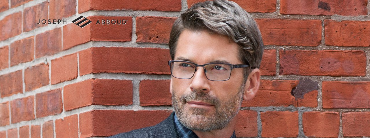 man with 5 o'clock shadow in front of brick wall wearing Joseph Abboud glasses