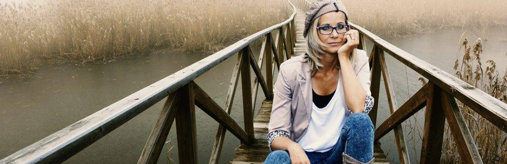woman on a bridge wearing glasses