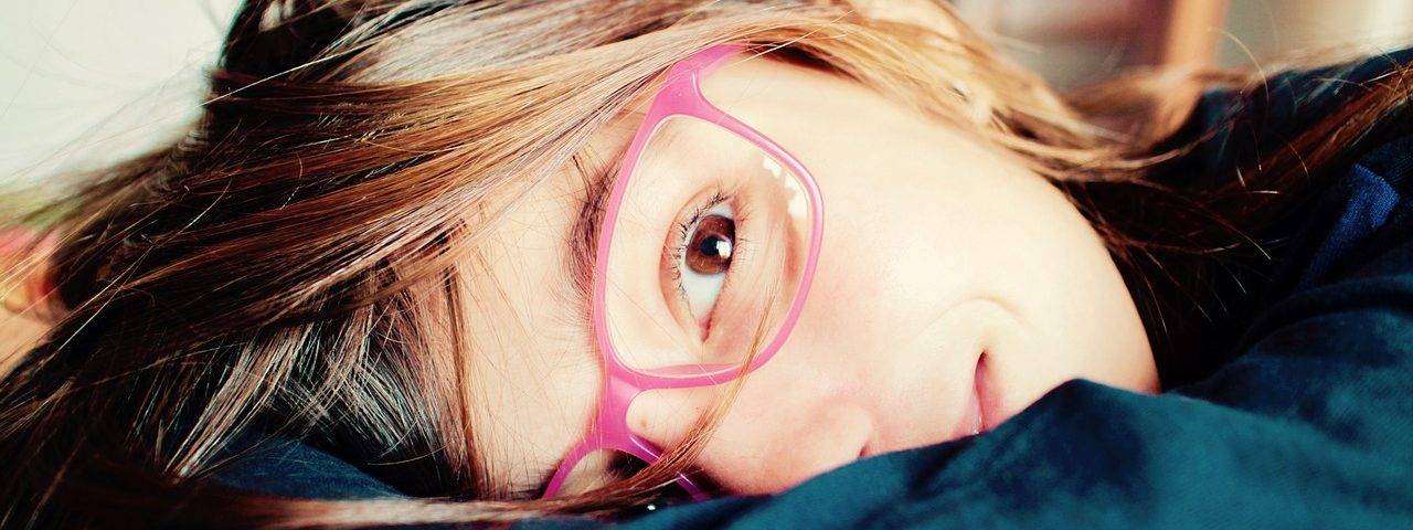little girl wearing pink glasses