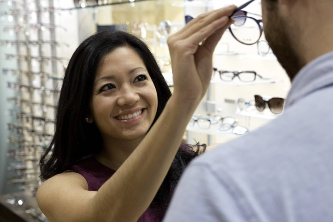 optical specialist fitting eyeglasses