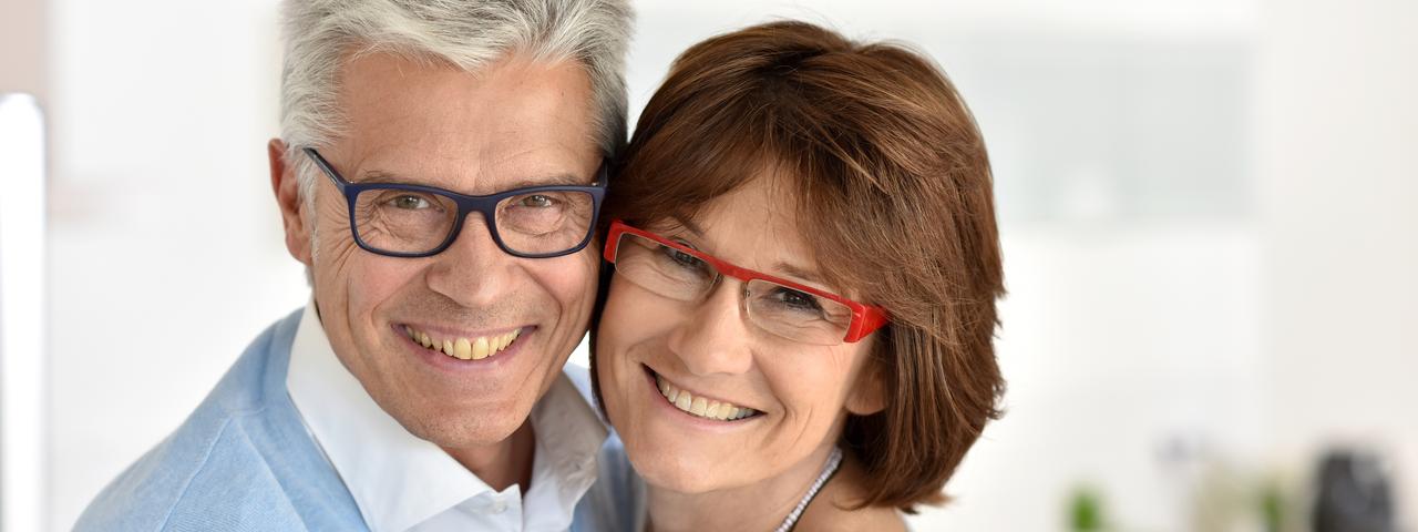 Happy senior couple wearing glasses