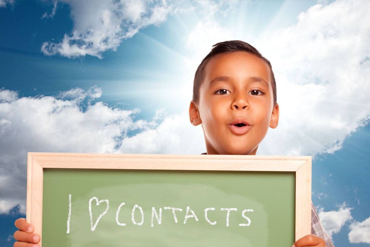 Child holding blackboard with I 'heart' Contacts
