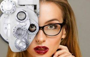 advertisement for eye care in huntington beach, ca with close up on blonde woman with red lips looking through eye exam technology while wearing eyeglasses