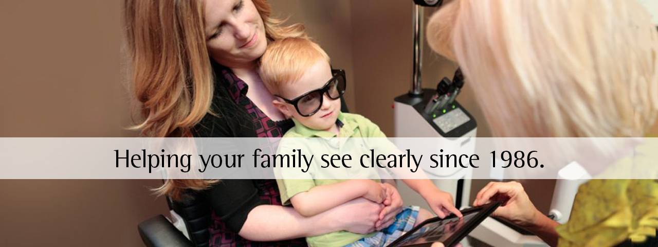boy wearing special glasses during eye exam with doctor