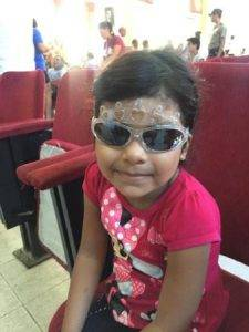 Girl with new sunglasses, donated by volunteer eye doctors from Colorado Springs, CO