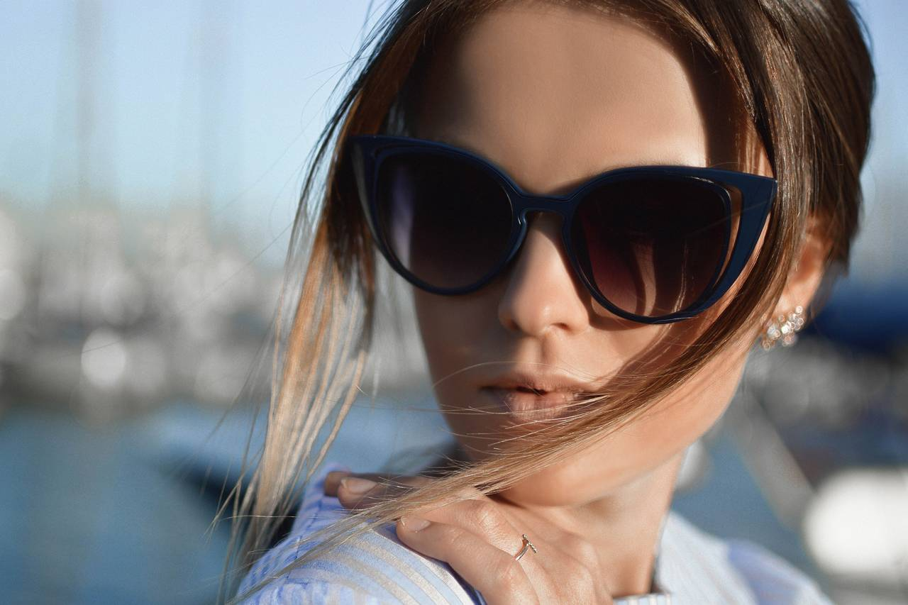 woman wearing sunglasses in front of blurred pier