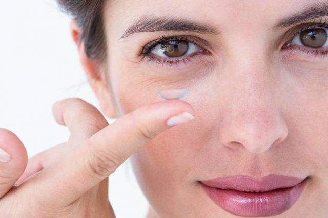 brunette woman holding contact lens in Davie