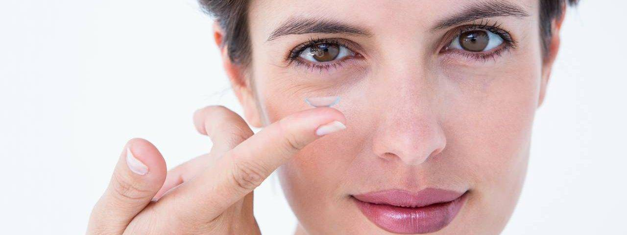 lady holding contact lens on finger smiling