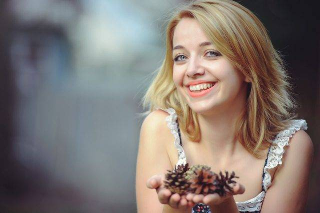 Woman Smiling Holding Pine Cone 1280x853 640x427