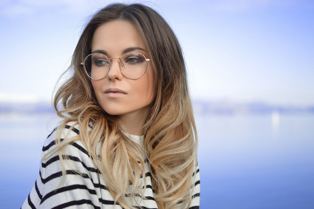 blonde woman wearing eyeglasses by waterfront
