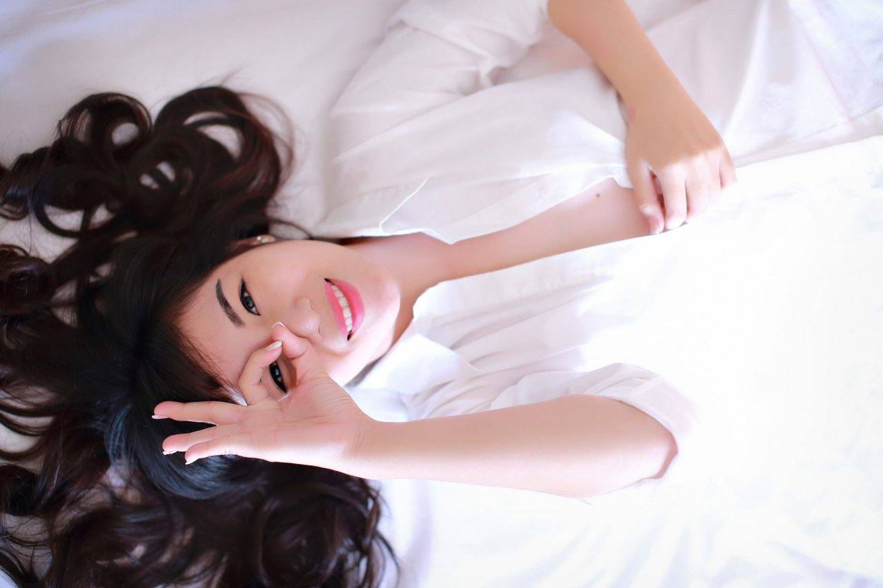 Asian female with finger circling eye smiling