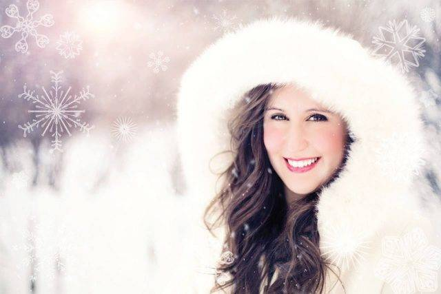 woman wearing white hood in winter smiling showing white teeth