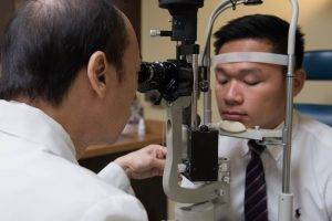 Optometrist giving an eye exam in Plano, TX