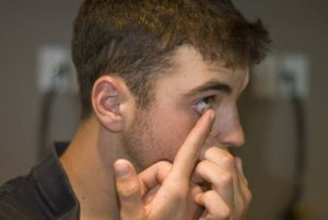 man removing contact lens in marion