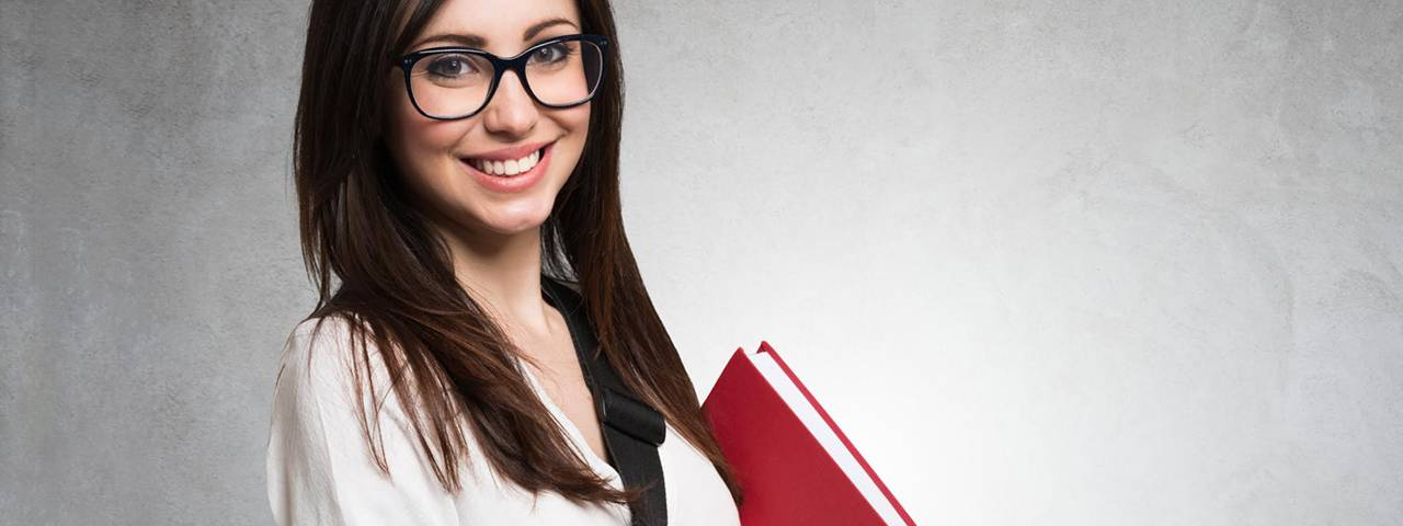 pretty brunette wearing eyeglasses and holding a red book