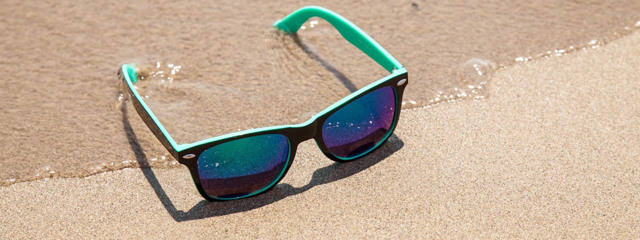 blue_sunglasses_sandy_beach_1280x480