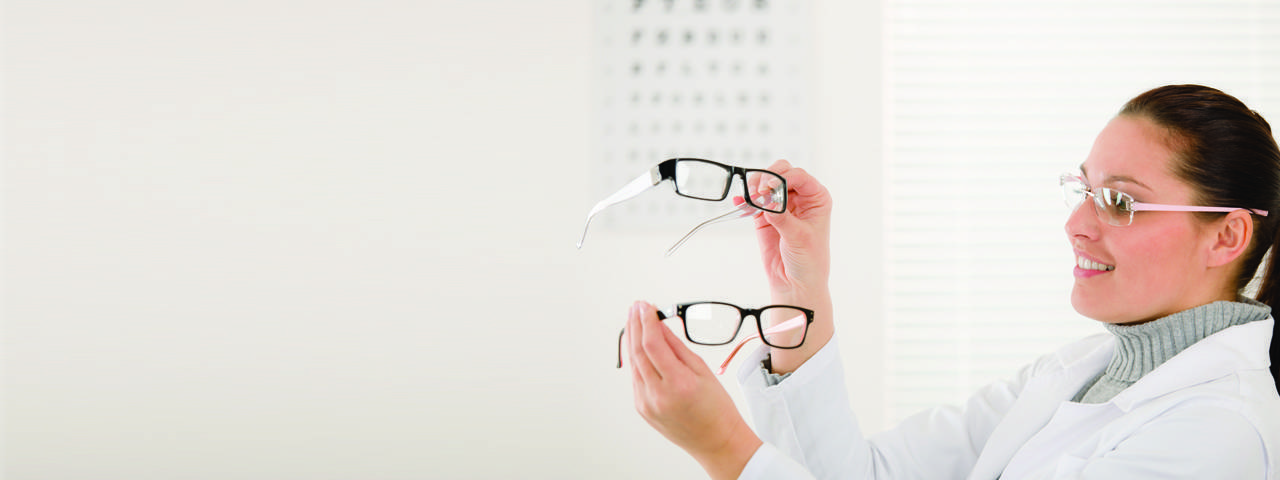 Woman comparing eyeglasses in Hattiesburg