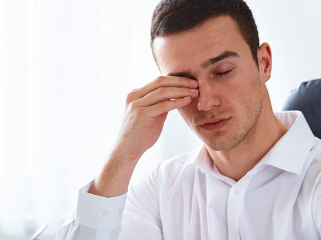 man rubbing eyes due to dry eyes