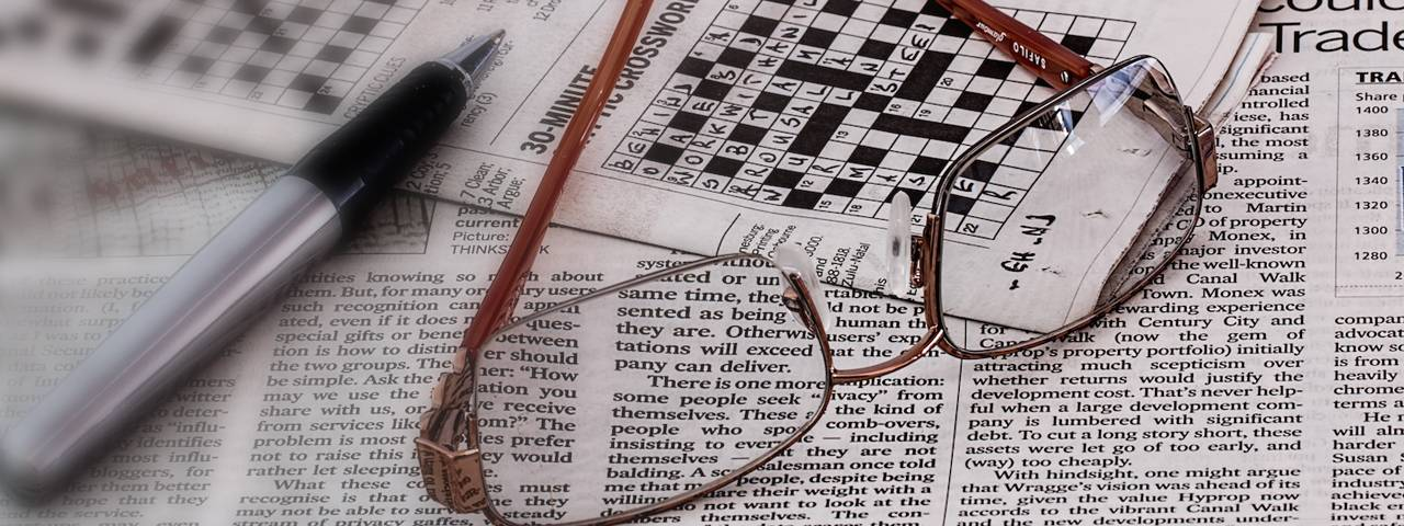 newspaper crossword and glasses 1280x480