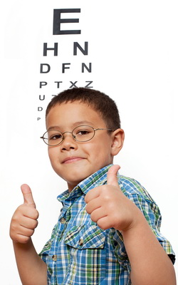 Eye Exam Chart in Port Colborne ON behind Happy Boy Wearing Glasses