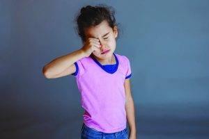 Eye doctor, little asian girl rubbing her eyes in Waco, TX