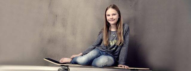 Optometrist, teenage girl sitting on her skateboard in Plainview, NY