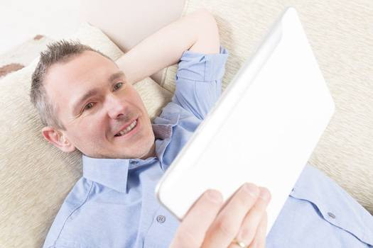 man with hearing aids tablet relax