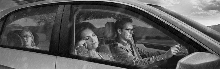 black and white photo of man and woman driving wearing drive safe lenses