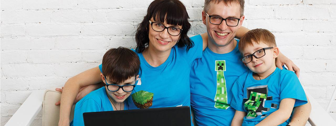family wearing eyeglasses looking at computer