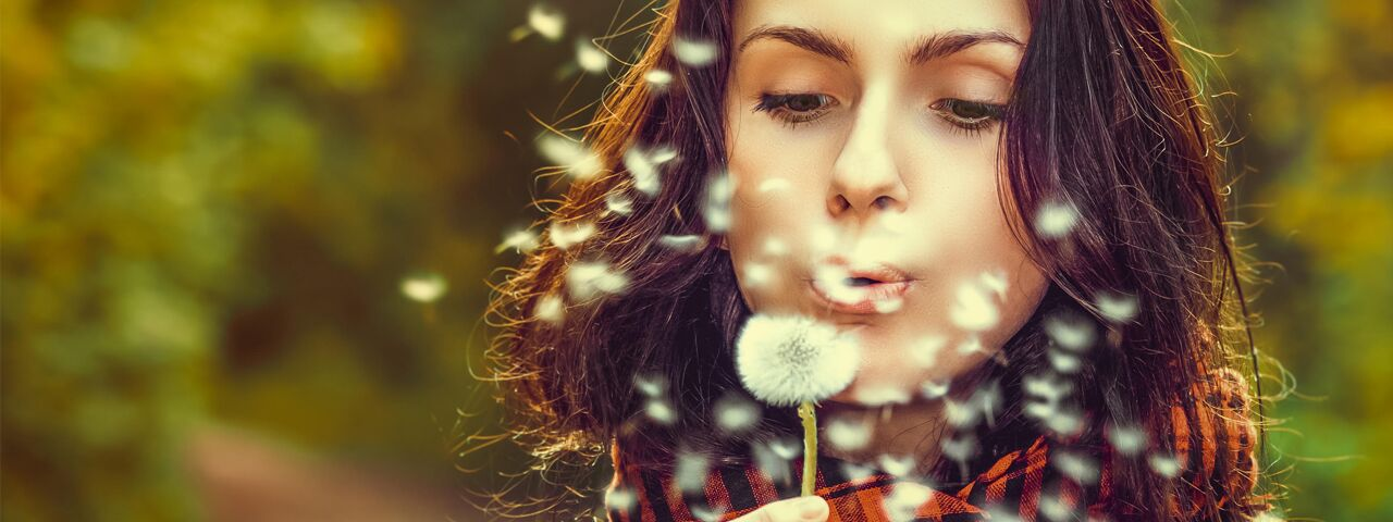 Woman blowing a dandelion in Camp Pendleton, CA