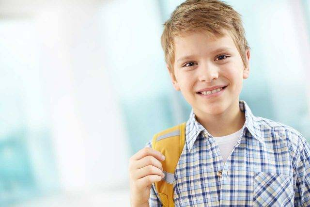 Boy on his way to school, wearing contact lenses for myopia control in Waterloo, ON