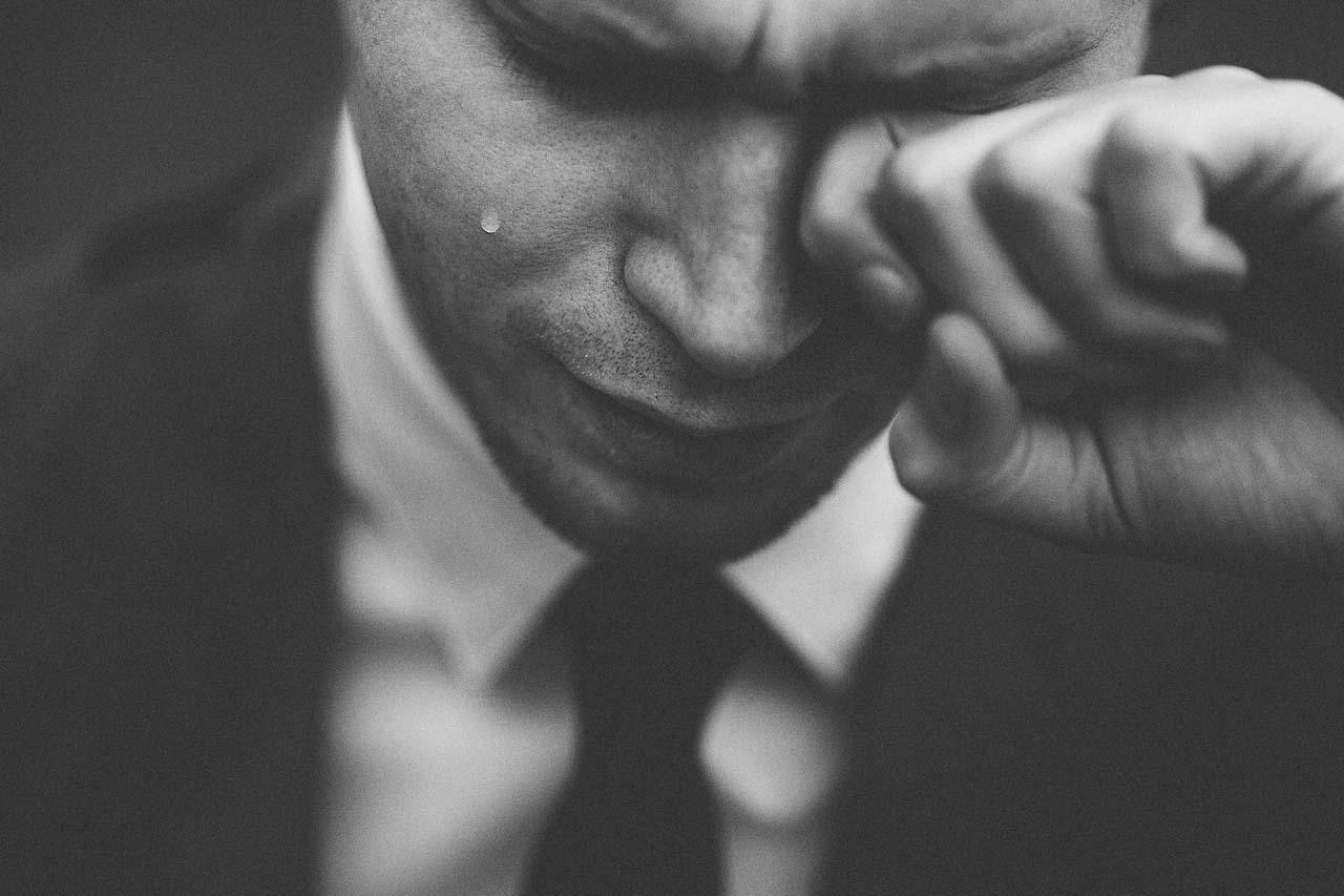 man with tear rubbing eye