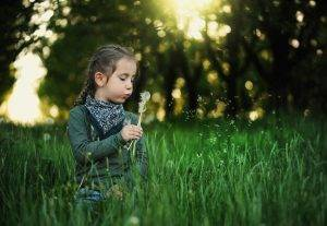 Young Girl blowing dandelion