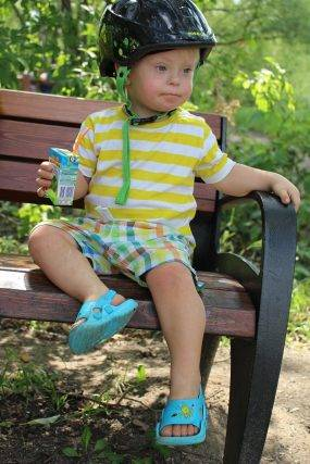 special needs child sitting on bench