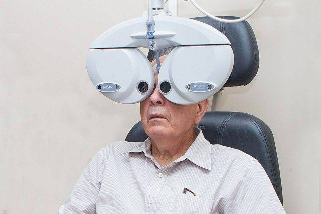 Eye exam, senior man using a phoropter in Coppell, TX