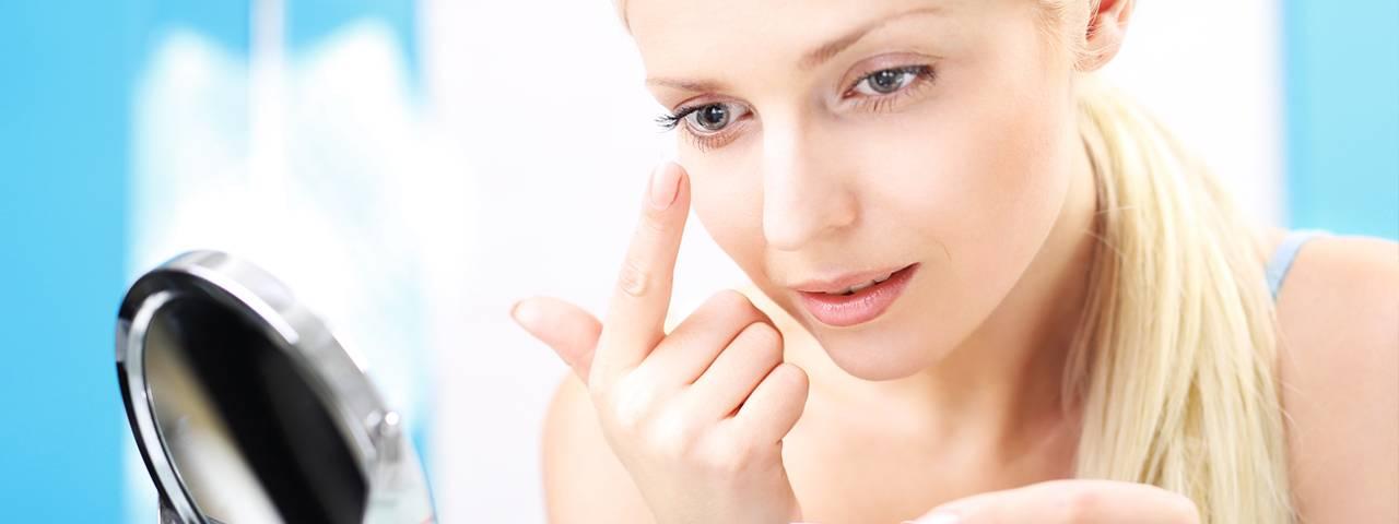 Woman applying contact lens, eye doctor, Freelton, ON