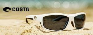 white Costa sunglasses on the beach