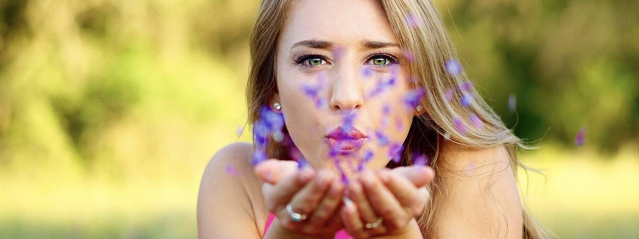 Eye care, woman with eye allergies blowing flowers in Orlando & Lake Mary, FL