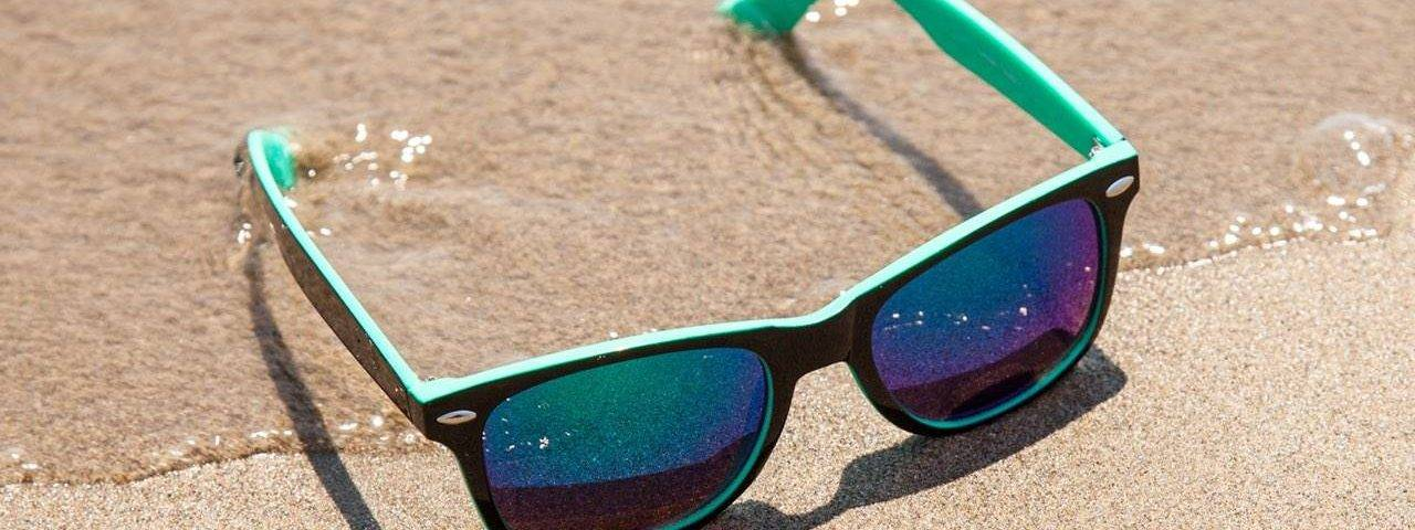 blue_sunglasses_sandy_beach-1280x480