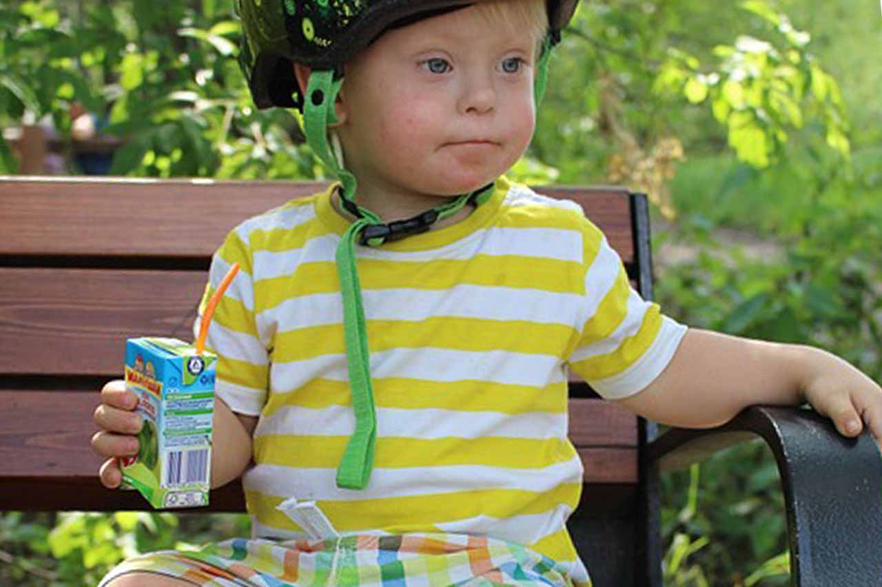 boy with down syndrome and juice drink
