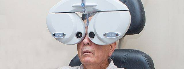 Eye doctor, senior man using a phoropter in Fort Lauderdale, FL